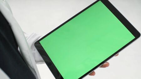Close up of modern black tablet with green screen and a man tapping on it with a stylus, modern technologies concept. Man hands holding a tablet with chroma key. 免版税图像