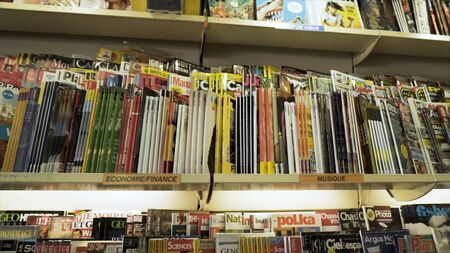 Magazines on display are being sold in a store , leisure and reading concept. Abundance of business, fashion, and lifestyle magazines are on market shelf at book store.