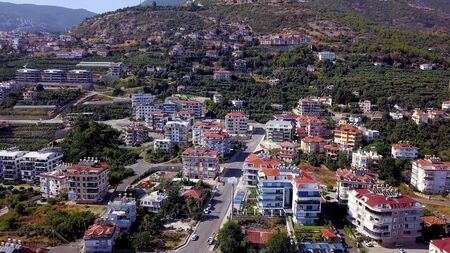 Top view of resort town on mountain green slopes. Clip. Beautiful modern city located on green slopes of mountains. Thriving resort town in mountains Stock fotó