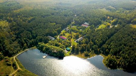 Old country resort in forest by lake. Stock footage. Top view of picturesque recreation center located by lake. Wonderful vacation in countryside in camp in sunny weather