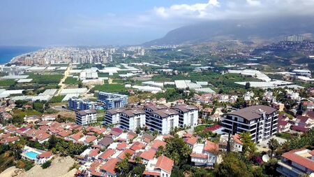 Top view of agricultural city by sea. Stock footage. Agricultural fields with greenhouses are located in city on coast of blue sea. Beautiful landscape of southern modern city with agriculture.