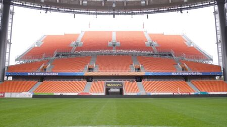 Outdoor stadium with football field and stands. Action. Inside view of football stadium with many empty stands and green field. Architecture of football stadium inside.