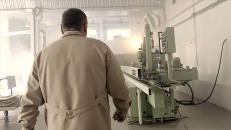 Man in industrial enterprise with machines. Action. Foreman goes to his office through machines in industrial enterprise. Rear view of chief who came to work in industrial enterprise Banco de Imagens