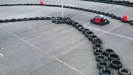 Unknown pilots competing in Karting Championship on a track made of old black car tires, aerial view. Media. Persons wearing protective uniform and helmet driving karts.