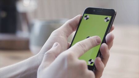 Close up of hands using smartphone with green screen, sliding and tapping on blurred kitchen table background. Stock footage. Man hands holding mobile phone with chroma key.