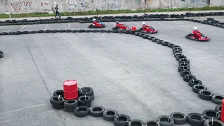Aerial view of a person driving red small go kart in protective uniform and a helmet on track side made of black tires. Media. Go kart racer struggling on circuit, motorsport concept. Stockfoto