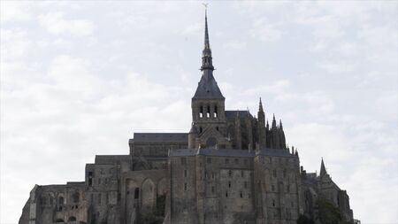 Mont Saint Michel, Normandy France, architecture concept. Action. Medieval abbey on the mountain of the same name on cloudy sky background. Reklamní fotografie