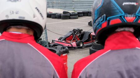 Close up of racer backs wearing special uniforms and helmets going to the kart cars, competition and race concept. Media. Rear view of two men before the karting race. Banco de Imagens