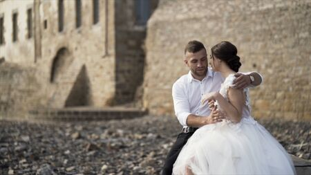 Outdoor photosession of loving stylish bride and groom on stony shore near the castle. Action. Beautiful wedding couple hugging and smiling, family and love concept.