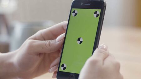 Close up of woman hands holding smartphone with green screen display in verical position. Stock footage. Female looking at her device with chroma key and traking marks. Imagens