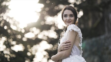 Portrait of a bride in a white wedding dress on a background of blurred green bushes and trees. Action. Sensual brown-haired girl looking aside, smiling and hugging herself, wedding concept.