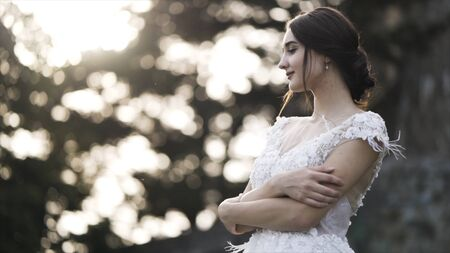 Beautiful bride in wedding dress on blurred background of bright sky and green tree leaves, marriage concept. Action. A portrait of a young pretty girl hugging herself and looking peaceful.