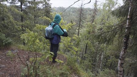 Male hiker with travel rucksack standing on the edge of high mountain during summer trek. Stock footage. Male explower standing on hill nd looking at tree tops.