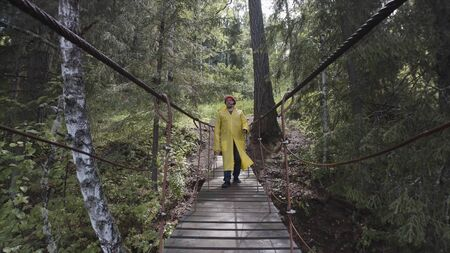 Natural lndscape of a young man in red hat and yellow jacket passing the suspension bridge in the forest, hiking concept. Tourist crossing the hanging bridge. Banco de Imagens