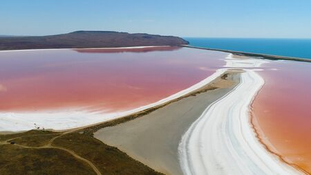 Panoramic aerial view of bright color famous natural place - pink lake in Crimea with amazing coastline and turquoise sea on the background. Unique pink lake with salt white banks.