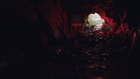 Man walking down inside the cave leaving the entrance behind him, extreme and sport concept. Stock footage. Tourist man in the underground cave with a red signal flare.