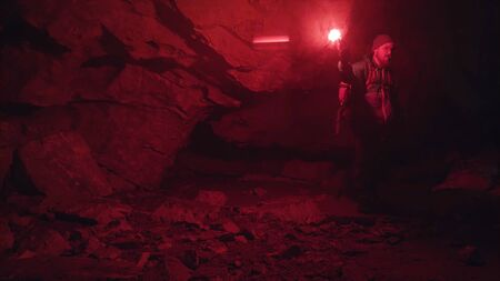 Silhouette of man with red burning signal flare walking on stones in the darkness of the cave, extreme tourism concept. Stock footage. Male explorer inside the underground tunnel.