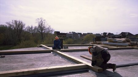 Framing crew rooftop prepairing wooden construction, measuring for better accuracy. Workers standing on the flat roof of the building and measuring wooden beam with a tape. Stock fotó