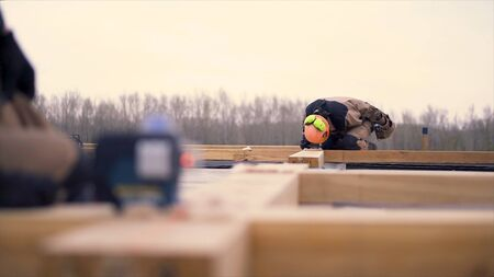 Close up of laser measurement level for construction works standing on a wooden bar at the construction site. Male builders making framework.