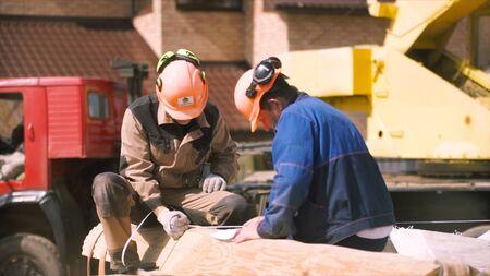 Men builders sitting on the wooden beam, house framework. Carpenters wearing uniform and protective helmet in front of crane machines. Reklamní fotografie