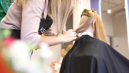 Young hairdresser giving a new haircut to female customer at parlor, beauty concept. Blonde female hairdresser holding scissors and comb at work. Banque d'images