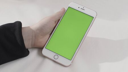 Hand holding touch green screen smart phone on white background. Stock footage. Hand with a cell phone with chroma key.