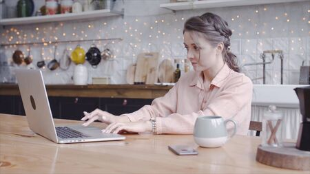 Young attractive woman working on laptop at home in kitchen. Stock footage. Beautiful woman carefully working on laptop in freelance mode and background of comfortable kitchen