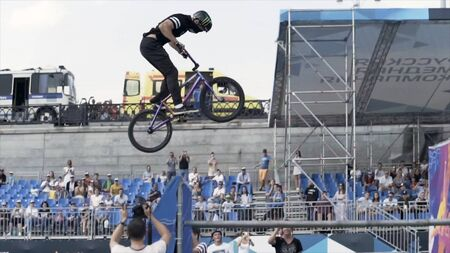 France - Paris, 08.15.2019: Side view of BMX rider performing dangerous trick in front of crowd during the competition. Action. Young risky teenager making death pool trick. Redactioneel
