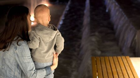 Rear view of young mother with her little son standing near the fountain in the late evening. Stock footage. Mom and her boy looking at the fountain.