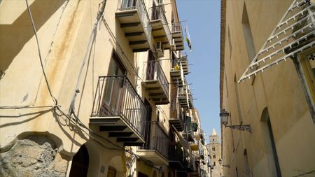 Narrow street with old urban architecture of european city. Action. Walls of houses are made of brown stone in old southern style of architecture. Vacation in warm historical city Banco de Imagens