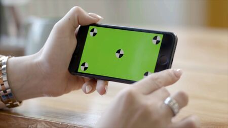 Close-up of woman holding phone with green screen. Stock footage. Beautiful female hand holding phone vertically with green screen. Watch videos on your phone