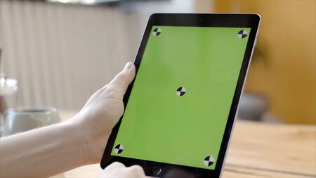 Man working with tablet tapping on green screen. Stock footage. Close-up of smooth hands holding and pressing on touch green screen of tablet