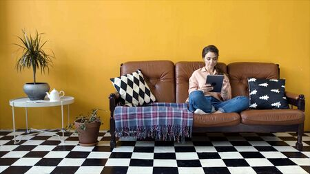 Young attractive woman sitting on couch working on tablet. Stock footage. Young woman in designer living room sits at tablet working freelance Stockfoto - 133566226