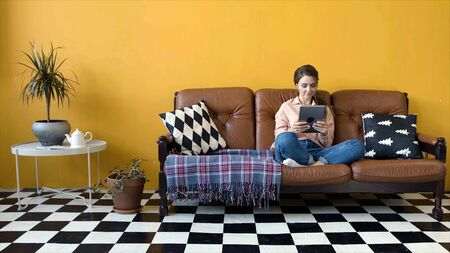 Young attractive woman sitting on couch working on tablet. Stock footage. Young woman in designer living room sits at tablet working freelance Stockfoto - 133566259