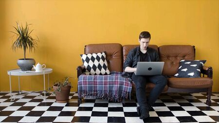 Young man working on laptop at home. Stock footage. Guy is working at home as freelancer on laptop sitting on couch. Modern style of work at home in freelance mode Stockfoto - 133566261