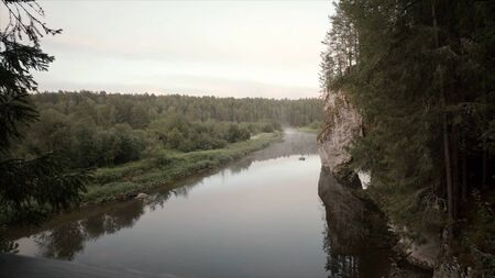 Landscape with river flowing in forest area in cloudy weather. Stock footage. Top view of forest valley with river and horizon with cloudy sky