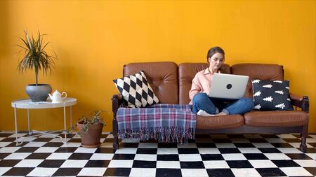 Young attractive woman working hard at laptop in living room. Stock footage. Beautiful young woman typing on laptop sitting on sofa in living room. Freelancer work at home on laptop Banco de Imagens