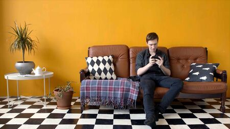 Guy plays game on phone sitting on couch. Stock footage. Young man enthusiastically plays phone sitting in stylish interior. Young man spends leisure time games on phone
