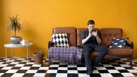 Guy plays game on phone sitting on couch. Stock footage. Young man enthusiastically plays phone sitting in stylish interior. Young man spends leisure time games on phone Stockfoto - 133566281