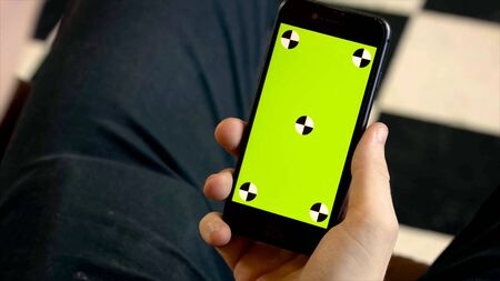 Close-up of man holding phone with green screen. Stock footage. Man holds new smartphone and looks at green screen with dots Stockfoto - 133566301
