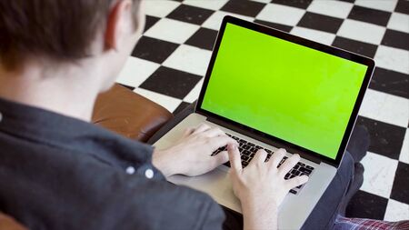 Close-up of young man typing at laptop with green scree. Stock footage. Young programmer or freelancer working at laptop with green screen