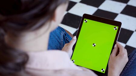Close-up of man holding tablet and touching green screen. Stock fooatge. Young freelancer uses tablet to work or create projects. Tablet with green screen to insert
