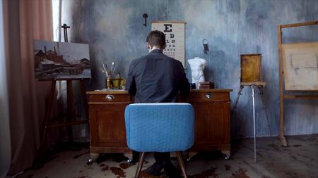 Rear view of artist sitting at desk. Stock footage. Man sits at table for drawing on old interior wall in artists room. Beautiful little sad room with paints, painting and sitting at table of artist Stockfoto - 133566306