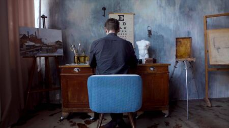 Rear view of artist sitting at desk. Stock footage. Man sits at table for drawing on old interior wall in artists room. Beautiful little sad room with paints, painting and sitting at table of artist Stockfoto