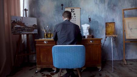 Rear view of artist sitting at desk. Stock footage. Man sits at table for drawing on old interior wall in artists room. Beautiful little sad room with paints, painting and sitting at table of artist Banco de Imagens