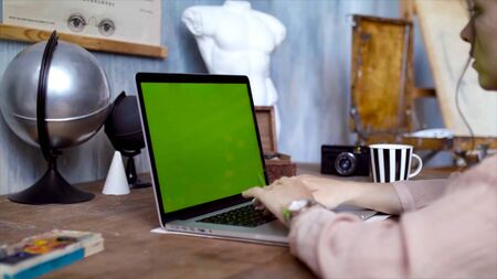 Young woman writing a text on her laptop with green screen. Stock footage. Young female employee engaged in creative work on laptop. Accelerated shooting Banco de Imagens