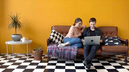Beautiful young couple sitting together at laptop on couch. Stock footage. Couple of students together watching something funny on laptop sitting on sofa in stylish living room Stock fotó