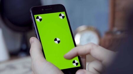 Man using mobile smartphone at home. Stock footage. Close up of a phone with a green screen in the hands of a man