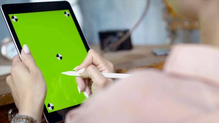 Hand draws a pencil on a tablet with a chromakey on the screen. Stock footage. Close up of a young woman drawing on a tablet with a green screen