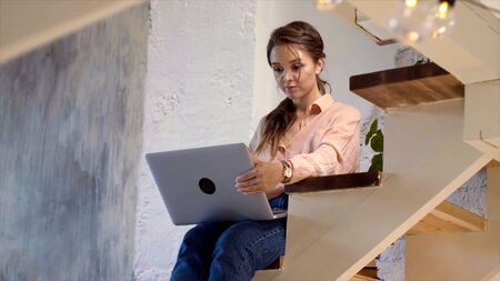 Girl using her laptop in her house. Stock footage. Young woman working at laptop at home Stockfoto - 133566372